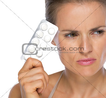 Portrait of thoughtful young woman with blistering package of pi