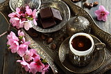 Turkish coffee, chocolate and branch with pink flowers.