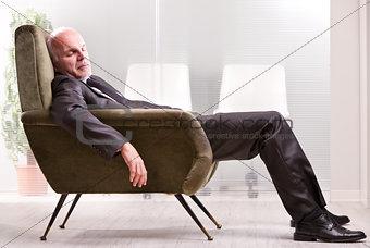 mature businessman asleep on an armchair