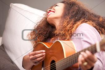 beautiful afroamerican girl having fun playing guitar