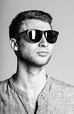 Portrait of handsome young man wearing sunglasses. Black and white