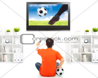 young fan watching soccer game at home