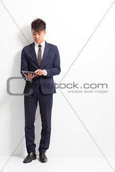 businessman using tablet and standing front of wall