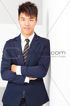 confident businessman cross arms with wall