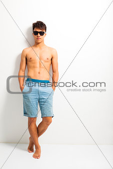 young man wear a sunglasses and standing near the wall