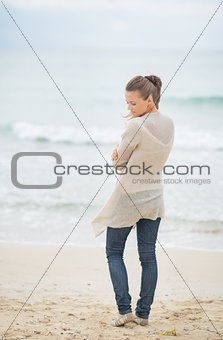 Young woman standing on cold beach