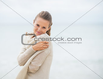 Portrait of happy young woman on cold beach
