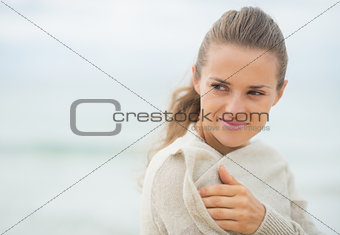 Happy young woman on cold beach looking on copy space