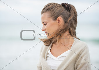 Portrait of relaxed young woman on cold beach