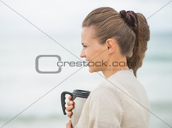 Happy young woman on cold beach with cup of hot beverage