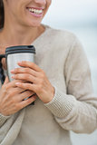 Closeup on happy young woman on cold beach with cup of hot bever