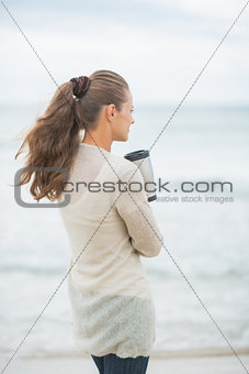 Young woman standing on cold beach with cup of hot beverage. rea