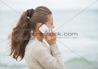 Young woman talking cell phone on cold beach