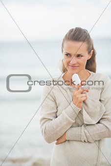 Thoughtful young woman with cell phone standing on cold beach