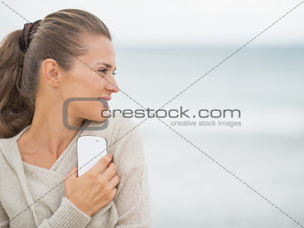 Young woman with cell phone standing on cold beach and looking o