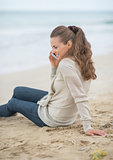 Young woman sitting on cold beach and talking mobile phone