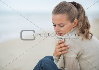 Portrait of calm young woman sitting on cold beach