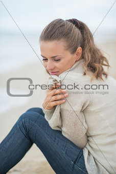 Calm young woman sitting on cold beach