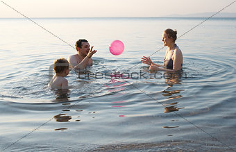 Young family playing with ball at sunset