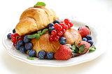 fresh croissant with berries for breakfast on vintage plate