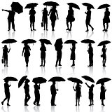 Set of black silhouettes of men and women with umbrellas. Vector