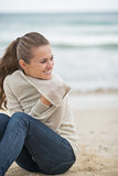 Happy young woman sitting on cold beach and looking into distanc