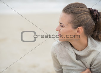 Calm woman sitting on cold beach and looking into distance