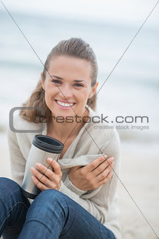 Happy woman sitting on cold beach with cup of hot beverage