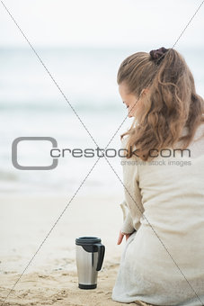 Woman sitting on cold beach with cup of hot beverage