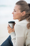 Calm woman sitting on cold beach with cup of hot beverage
