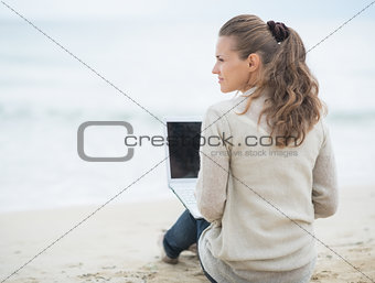 Young woman sitting with laptop on cold beach