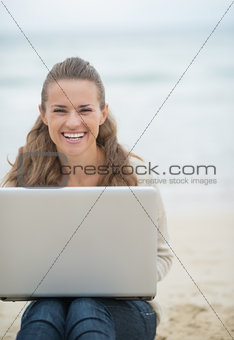 Happy young woman sitting with laptop on cold beach