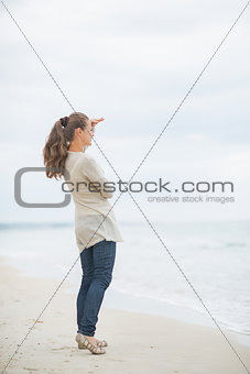 Full length portrait of young woman on cold beach looking into d