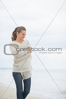 Young woman walking on cold beach