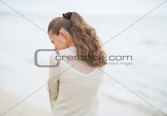 Closeup on young woman walking on cold beach. rear view