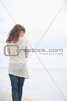 Young woman walking on cold beach. rear view