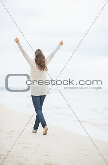 Full length portrait of young woman walking on cold beach. rear