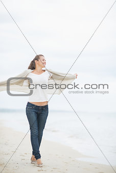 Full length portrait of young woman walking on cold beach and re