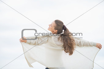 Young woman on cold beach rejoicing. rear view