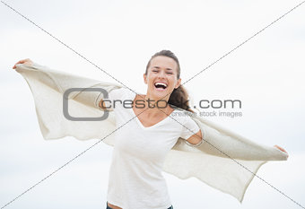 Happy young woman on cold beach rejoicing