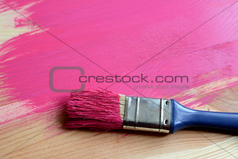 Paint-covered paintbrush on painted wood