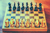 Ancient wooden chess standing on chessboard