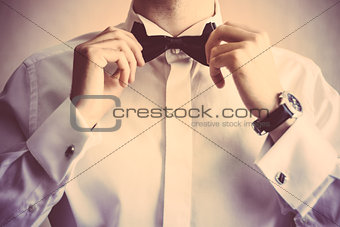 Closeup of business man adjusting neck bow