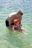 Father and little baby girl in sea