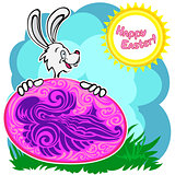 Bunny with patterned easter egg on a glade