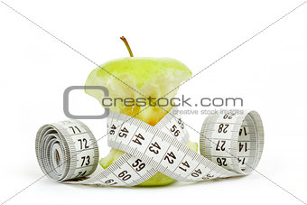 Green bitten apple isolated on white with measuring tape