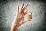 Hand holding locked padlock