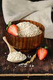organic oat flakes with strawberries on a wooden table, a healthy diet