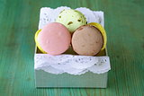 French multicolored macaroons cookies on a vintage wooden background