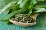 dry green basil in a wooden spoon